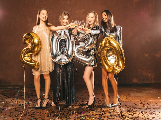 Beautiful women celebrating new year.happy gorgeous girls in stylish sexy party dresses Free Photo