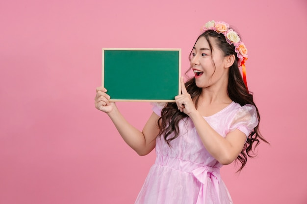 Beautiful women dressed in pink princess dresses hold a green board on a pink . Free Photo