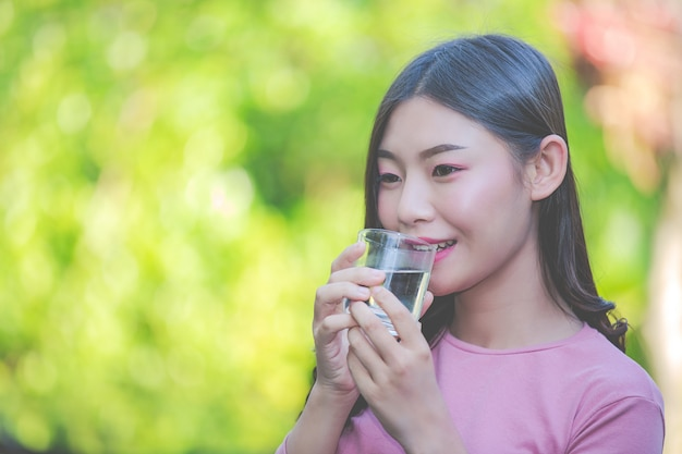 Beautiful women drink clean water from a glass of water Free Photo