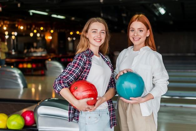 Belle donne che tengono le palle da bowling Foto Gratuite
