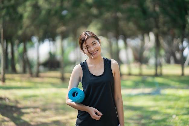 Beautiful women holding yoga mat prepare to exercise yoga in the garden Premium Photo