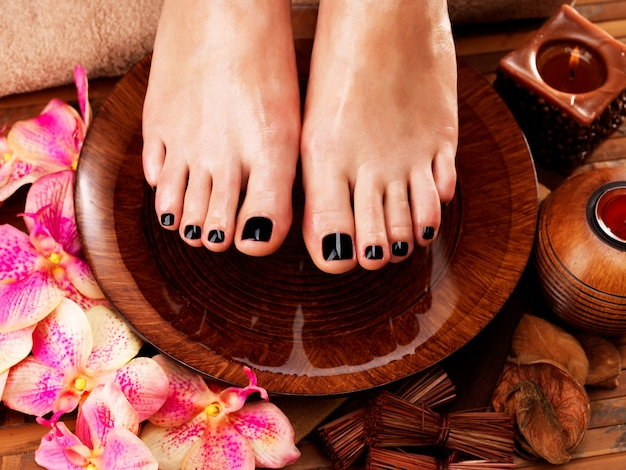 Beautiful women legs with black pedicure after spa procedures - spa treatment concept Free Photo