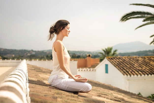 Beautiful women practicing meditation, sitting on a rooftop Premium Photo