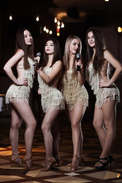 Beautiful women singing karaoke songs in microphones in restaurant Premium Photo