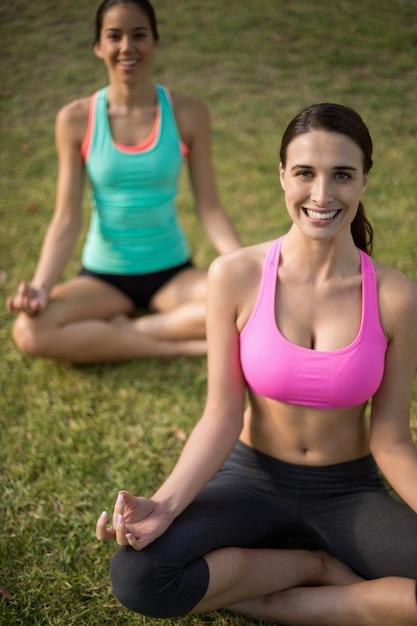 Beautiful women sitting on grass and doing meditation Premium Photo