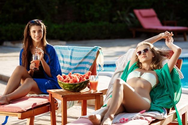 日光浴、リラックス、スイミングプールのそばの長椅子で休んで美しい女性 無料写真