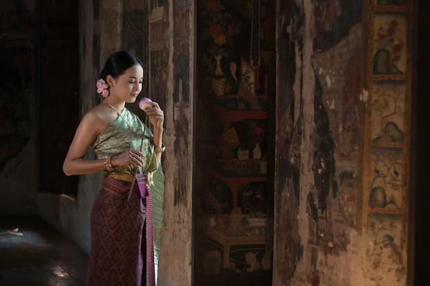 Beautiful women thai girl holding hand lotus in traditional thai costume with temple ayutthaya Premium Photo