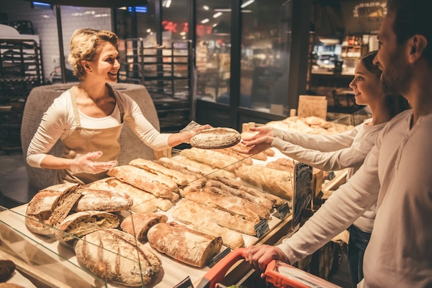 Beautiful worker is smiling while offering a bread. Premium Photo