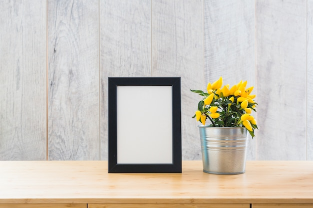 Beautiful yellow hot chili peppers in silver pot and white picture frame on the table Free Photo