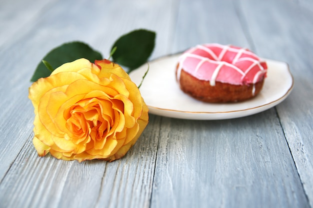 A beautiful yellow rose with an opened bud and a donut with pink icing on a white ceramic plate on a gray wooden Premium Photo