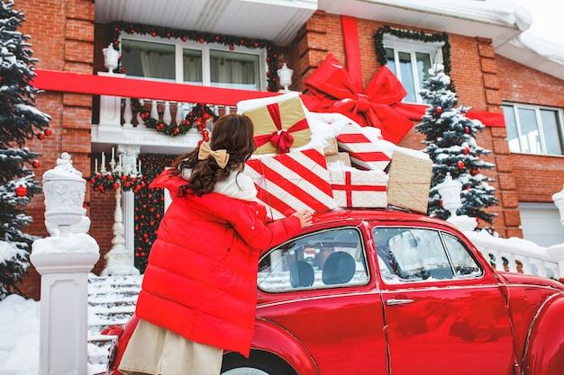 Красивая молодая взрослая девушка, веселая и счастливая у красной машины на фоне дома в рождественских украшениях Premium Фотографии