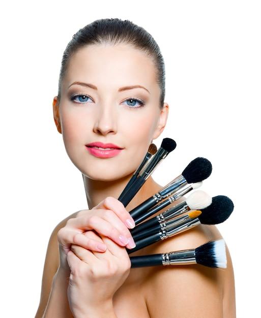 Красивая молодая взрослая женщина держит кисти для макияжа возле лица, изолированного на белом Бесплатные Фотографии