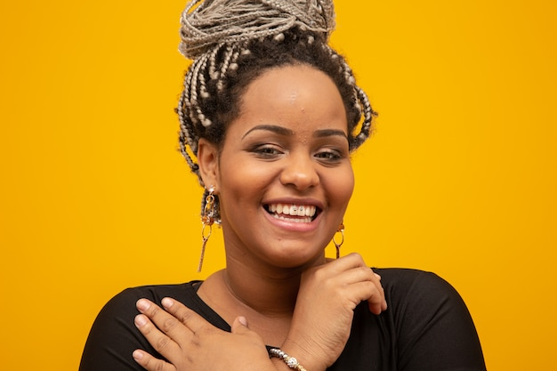 Beautiful young african american woman with dread hair on yellow Premium Photo