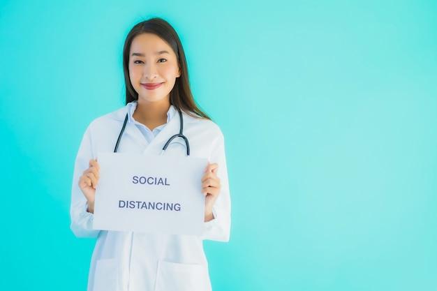 社会的な距離と記号の紙の美しい若いアジア医師女性 無料写真