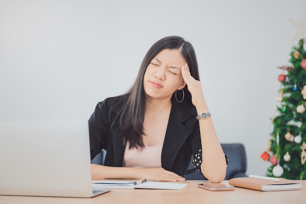 Beautiful young asian girl feeling headache and stress in office space with laptop and decorate christmas tree background Premium Photo