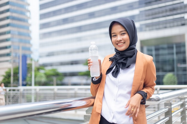 Beautiful young asian muslim with bottled water. Premium Photo