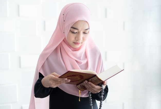 Beautiful young asian muslim woman reading quran Premium Photo