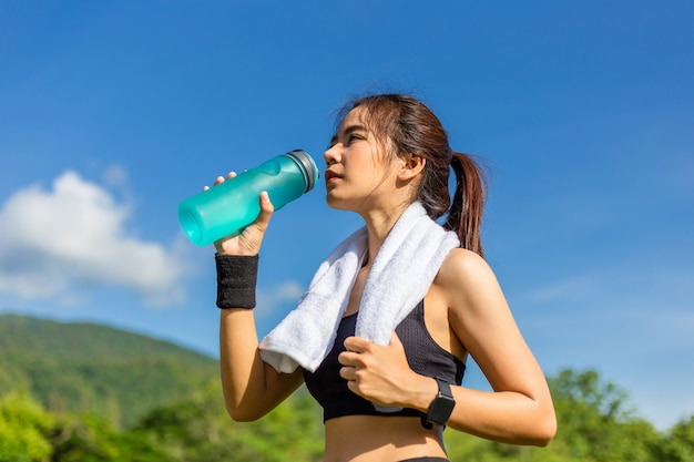 Beautiful young asian woman exercising in the morning at a running track, taking a rest to drink water Premium Photo