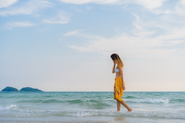 Beautiful young asian woman happy relax walking on beach near sea. Free Photo