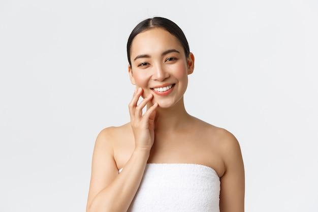 バスルームに立って、幸せな笑顔、きれいな肌に触れるタオルで美しい若いアジア女性は、体、白い壁の世話をしてバスルームにスキンケア製品を適用します。 Premium写真