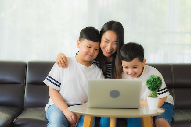 Beautiful young asian woman mom with her sons using a laptop Free Photo