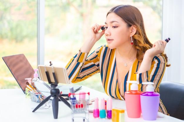 Красивая молодая азиатская женщина кладя ее составляет во время ее онлайн обзора продукта красоты дома Premium Фотографии