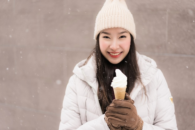 Beautiful young asian woman smile and happy with ice cream in snow winter season Free Photo