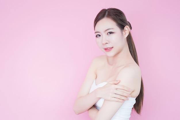 きれいな新鮮な肌の顔自然化粧品で美しい若いアジア女性笑顔 Premium写真
