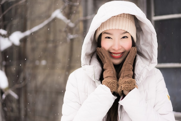 Beautiful young asian woman smiling happy for travel in snow winter season Free Photo