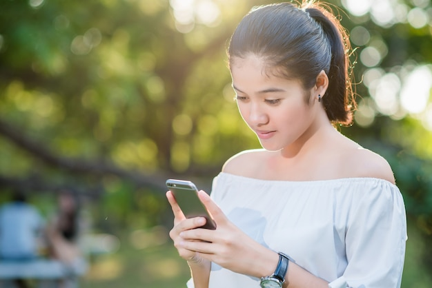 Beautiful young asian woman smiling while reading her smartphone in a garden. Premium Photo