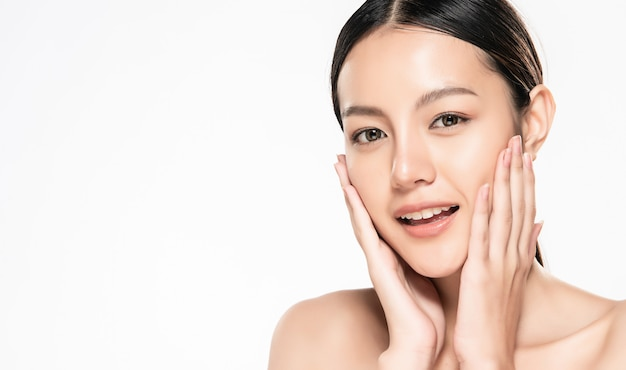 Beautiful young asian woman touching her clean face with fresh healthy skin, isolated on white Premium Photo