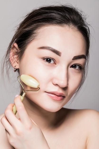 完璧な肌にヒスイのフェイスローラーを使用して美しい若いアジア女性。美容顔のクローズアップ。半貴石を使ったフェイシャルトリートメントのコンセプト。コピースペースと灰色に分離 無料写真