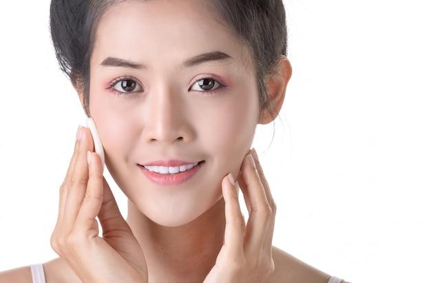 自分の顔にパウダー、スポンジ、化粧品を使った美しい若いアジア女性 Premium写真