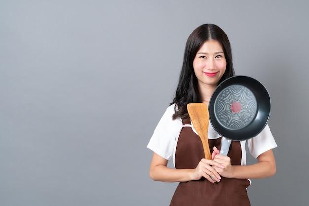 회색 배경에 검은 팬과 나무 주걱을 들고 손으로 앞치마를 입고 아름 다운 젊은 아시아 여자 프리미엄 사진