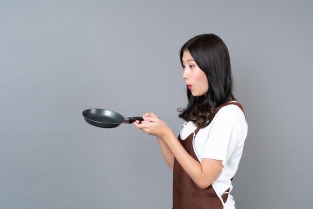 회색 배경에 검은 팬을 들고 손으로 앞치마를 입고 아름 다운 젊은 아시아 여자 프리미엄 사진