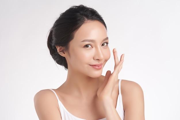 白い背景、顔のケア、フェイシャルトリートメント、美容、美容、スパ、アジアの女性の肖像画の清潔でさわやかな肌を持つ美しい若いアジア女性 Premium写真