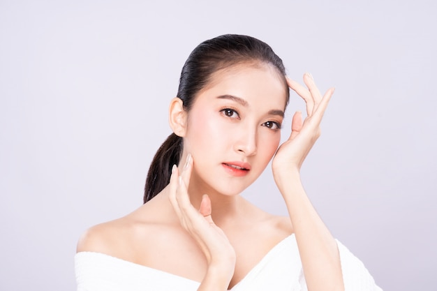 Beautiful young asian woman with clean fresh white skin face in beauty pose touching shoulder with finger. Premium Photo