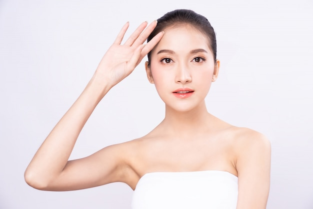Beautiful young asian woman with clean fresh white skin raising her arm and hand in protection sunshine in isolated white background. Premium Photo