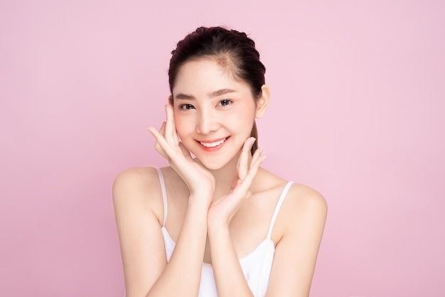 Beautiful young asian woman with clean fresh white skin touching her own face softly in beauty pose touching with fingers in pink background. Premium Photo