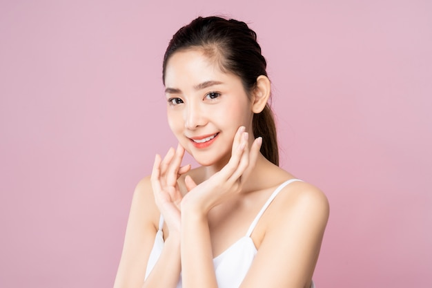 Beautiful young asian woman with clean fresh white skin touching her own face softly in beauty pose. Premium Photo