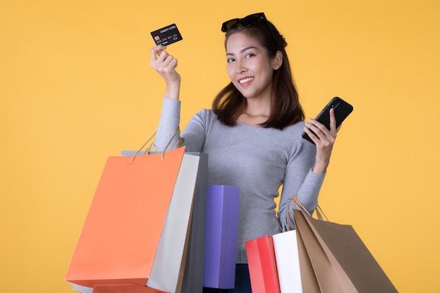 Ảnh người phụ nữ châu Á trẻ đẹp với túi mua sắm đầy màu sắc với điện thoại thông minh và thẻ tín dụng