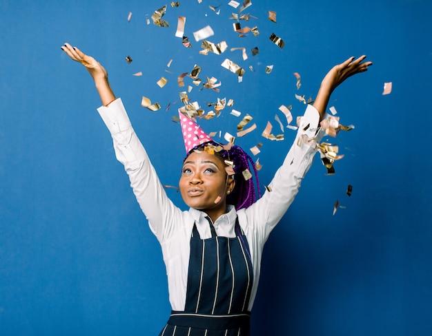 푸른 공간을 통해 격리 된 카메라에 색종이 장식을 불고있는 동안 생일이나 새해와 Chrismas 파티를 축하 아름다운 젊은 흑인 여성 프리미엄 사진