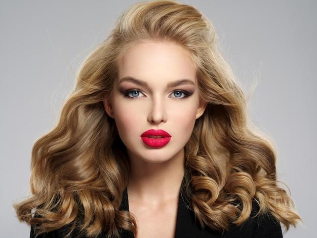 섹시 한 붉은 입술으로 아름 다운 젊은 금발 소녀. 긴 머리를 가진 백인 여자의 근접 촬영 매력적인 관능적 인 얼굴. 스모키 아이 메이크업 무료 사진