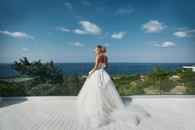 立っていると海を見てウェディングドレスの美しい若いブロンドモデルの女性 Premium写真