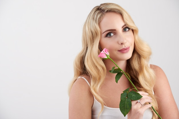 Beautiful young blonde caucasian woman in camisole top posing with pink rose Free Photo
