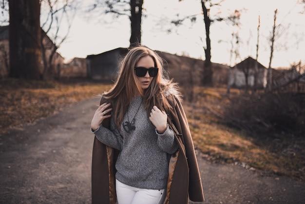 美しい若いブロンドのモデルの女の子。白いズボン。グレーのニットセーター。黒いブーツ。黒のサングラス。馬の形をした首の木製ペンダント。茶色のコートでポーズ。日没時。ポートレート Premium写真