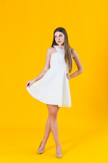 Beautiful young blonde woman in nice spring dress, posing on yellow background in studio Premium Photo
