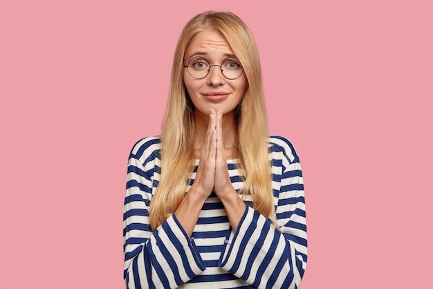 Красивая молодая блондинка позирует у розовой стены Бесплатные Фотографии