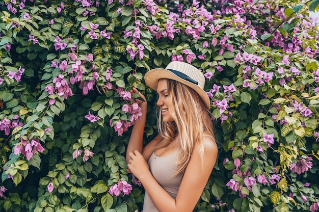 Beautiful young blonde woman posing with tropical flowers Premium Photo