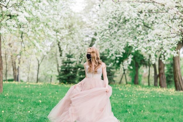 ウェディングドレスと咲くリンゴの木の近くの彼女の顔に黒い医療マスクの美しい若い花嫁。 covid19防止。 Premium写真